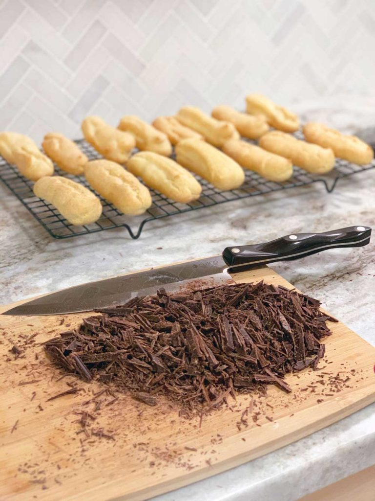 shaved chocolate pieces with plain choux pastry cases behind