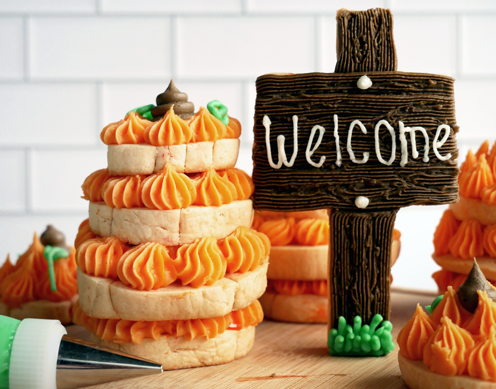 No spread cut-out sugar cookie stacks with buttercream into 3D pumpkins.