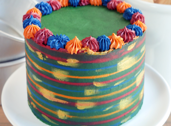 Nutty Orange Chocolate Cake with Pistachio Cranberry Filling and White Chocolate Buttercream, Decorated with a Fall/Winter Themed Striped Buttercream and Gold Luster Dust Painted Design