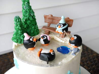 Delicious peppermint hot chocolate cake with chocolate ganache, marshmallowy swiss meringue buttercream, and crunchy peppermint candy filling. Decorated with an adorable fondant and isomalt penguin ice skating rink!