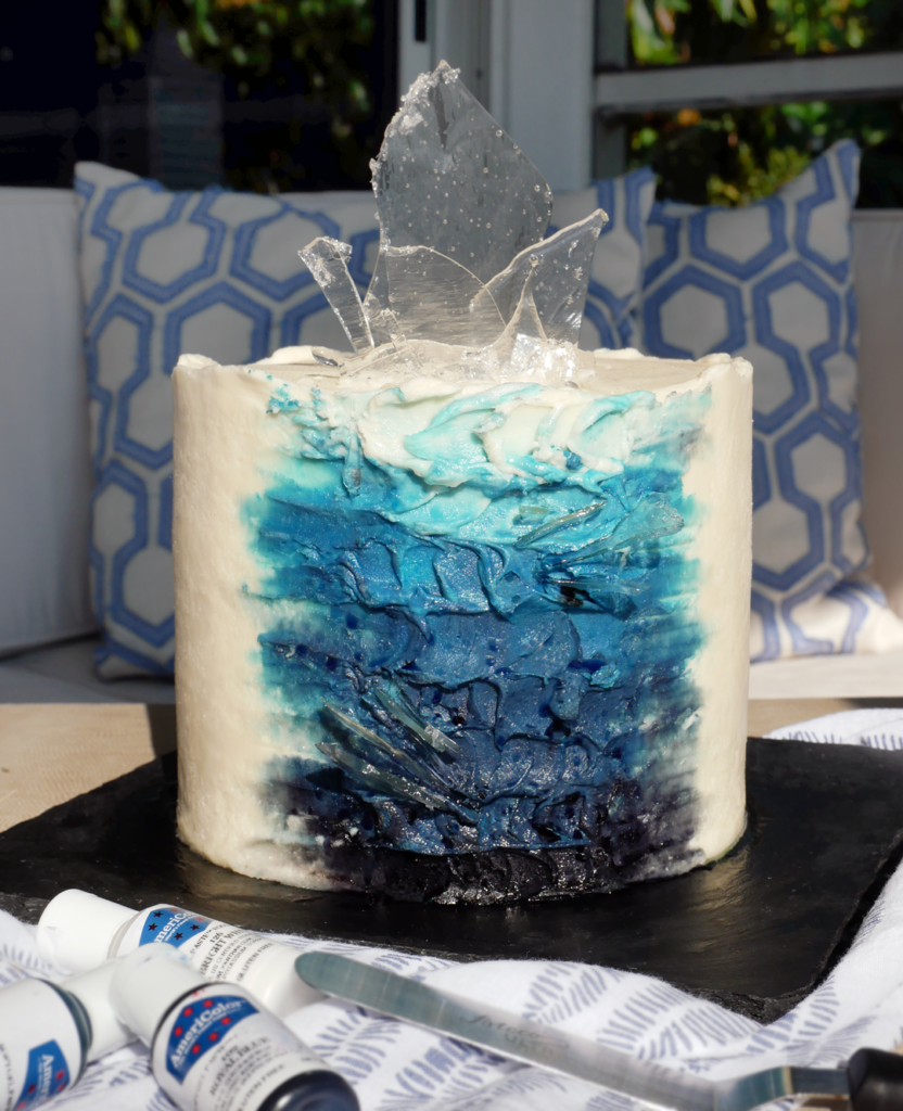 buttercream painted glacier inspired cake with palette knife painting tehcniques and isomalt sugar sail