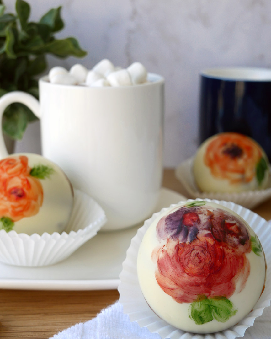 Painted with edible cocoa butter paint, a floral hot chocolate bomb sits in front of a mug filled with hot chocolate. There is more white chocolate in the background, also painted with warm flowers.