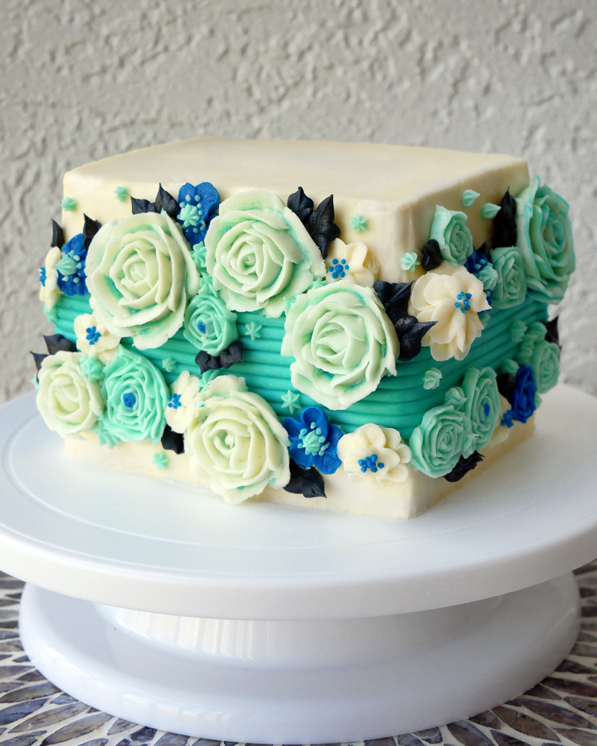 A square cake with beautiful wintery buttercream flowers and a textured stripe down the middle! The perfect winter floral cake.