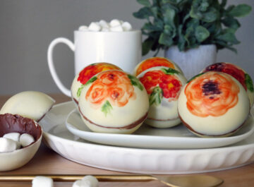 Colorful flowers are painted with cocoa butter on double chocolate hot chocolate bombs.