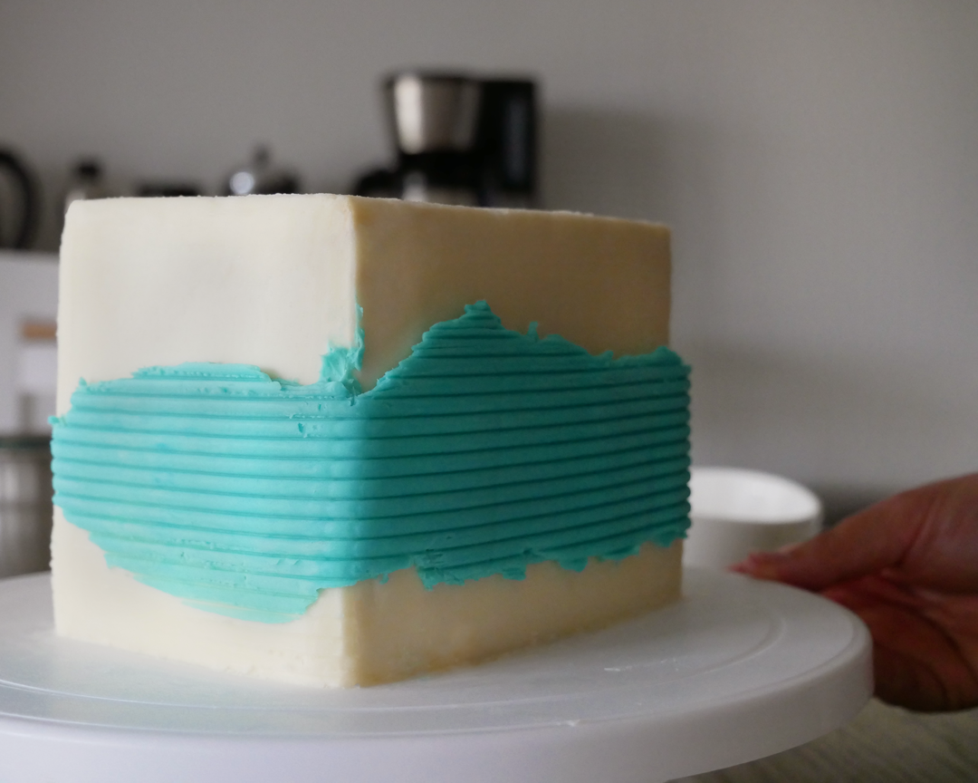 A white square buttercream cake with a blue textured line of buttercream down the center made by a textured cake scraper.