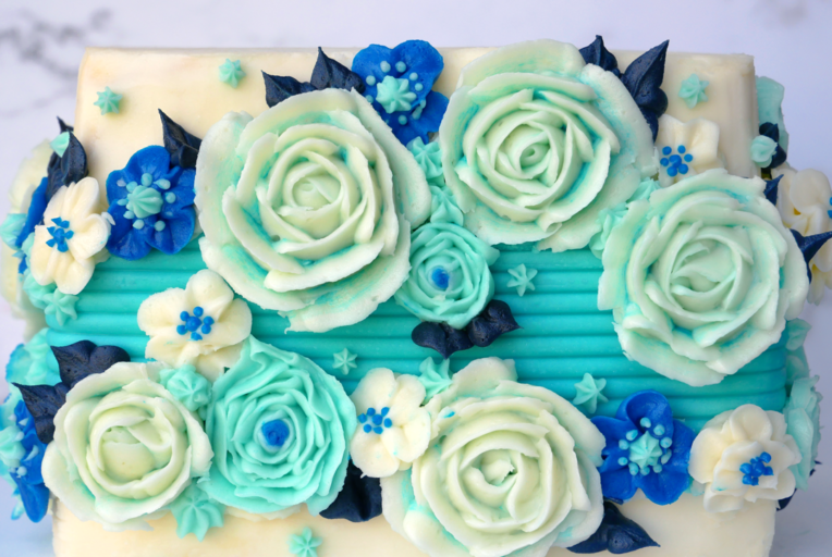 Wintery light blue and dark blue buttercream flowers decorate a white square buttercream cake with a blue textured stripe down the middle.
