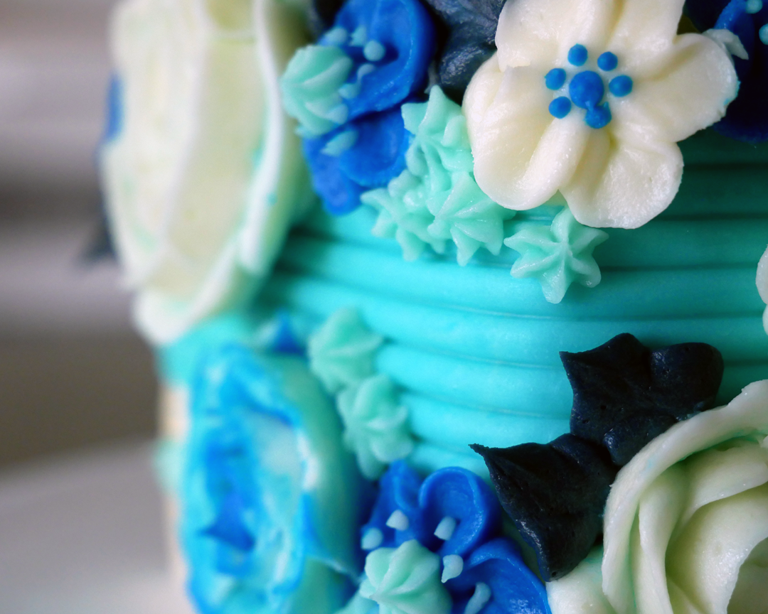 Winter blue buttercream flowers up close on top of a textured/striped blue buttercream made with a cake comb.