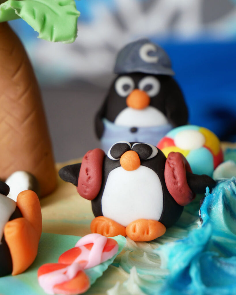 Penguins on Vacation - fondant penguins at a beach scene, on a triple chocolate oreo crunch cake decorated with white chocolate buttercream to look like sand and ocean waves.