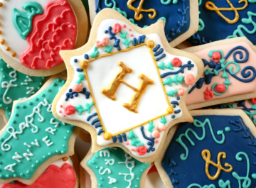 Royal icing decorated cookies - sugar cookies decorated with blue, pink, and gold royal icing for a monogram anniversary gift.