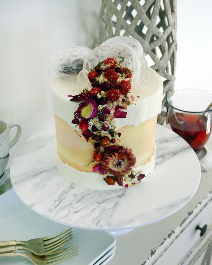Youthberry Tea white cake with raspberry filling and orange faux swiss meringue buttercream, topped with isomalt teabag bombs and edible flowers.