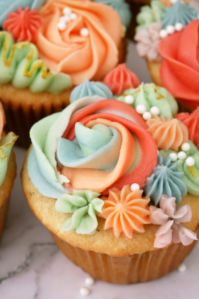 Colorful spring piped cupcake set, featuring peach jam filled Magnolia bakery-style cupcakes, topped with gold luster dust and Brandy buttercream flowers!