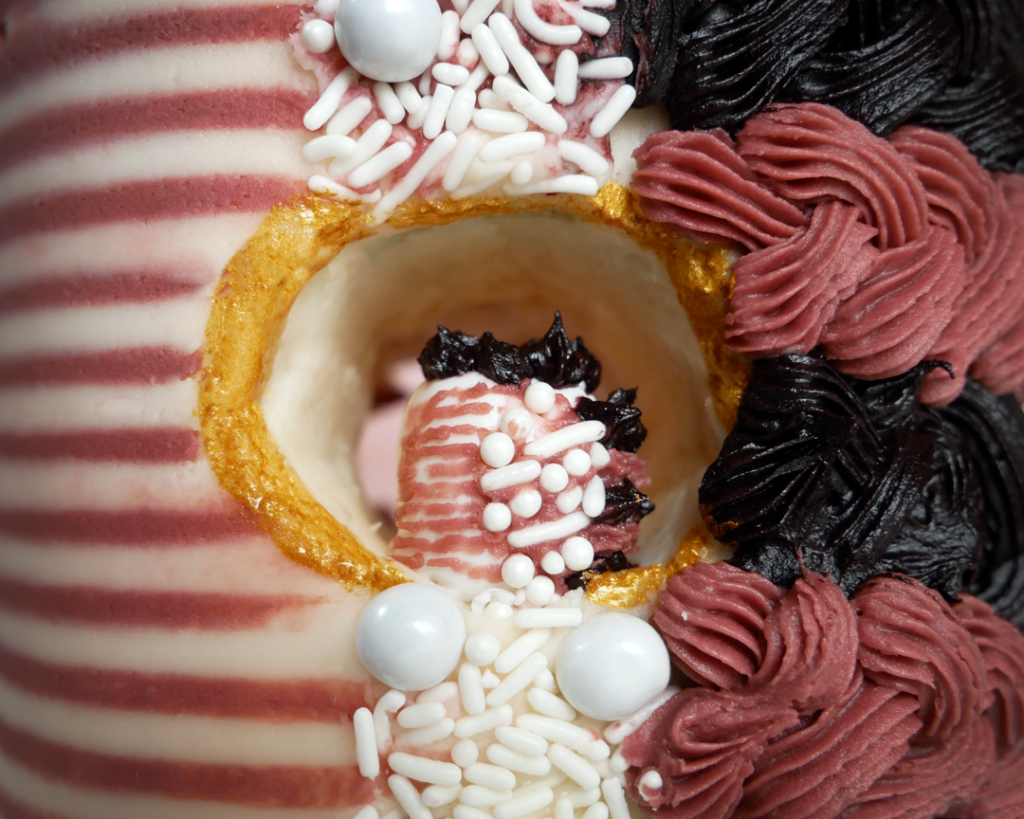 A mini striped cake with a horizontal hole through the middle and an even smaller cake inside of it.