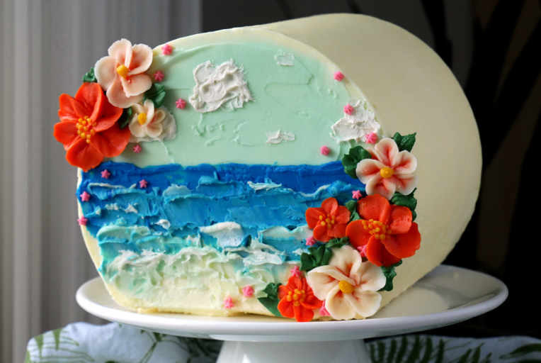 This Hawaiian beach and buttercream flower cake is painted with palette knives and decorated sideways as a sideways cake top forward design!